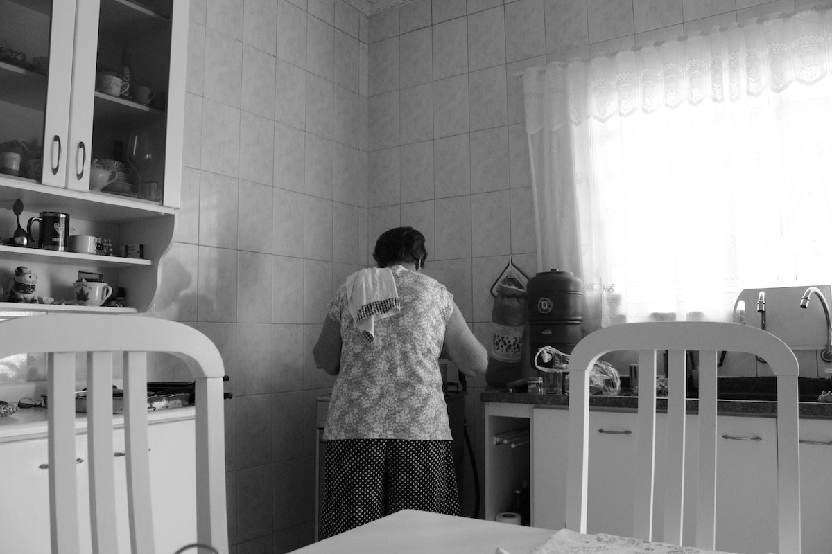 Woman cooking in kitchen with back turned to the camera