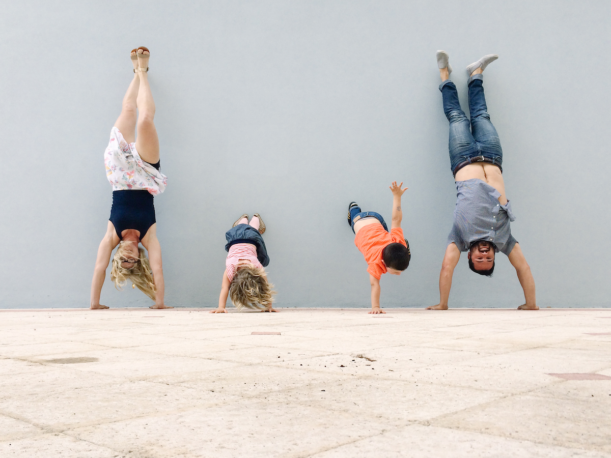 Family upside down doing handstands against wall