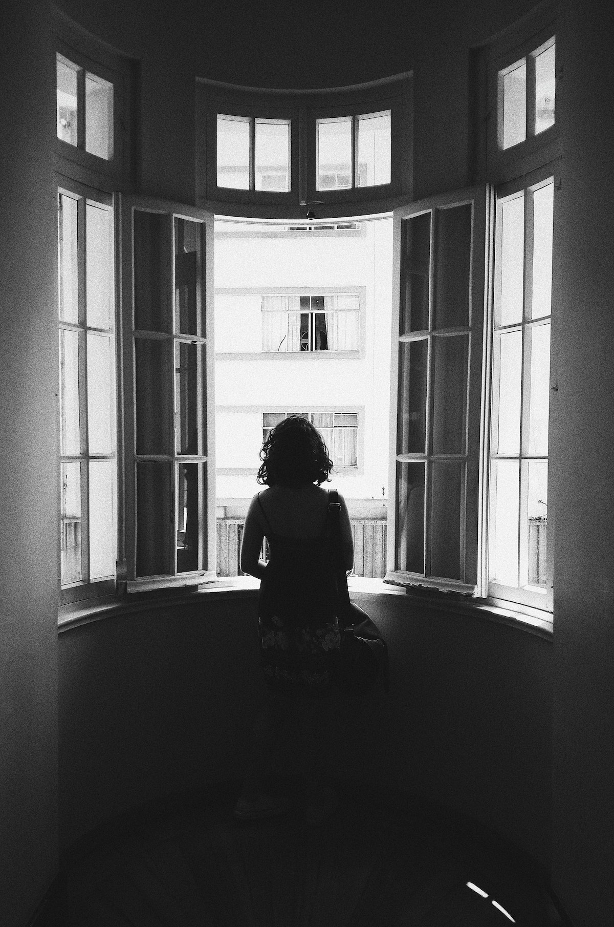 Silhouette of woman staring out apartment window