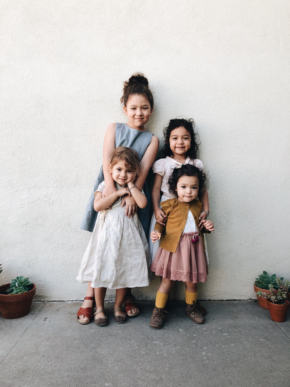 Four children lined in front of wall for family photo