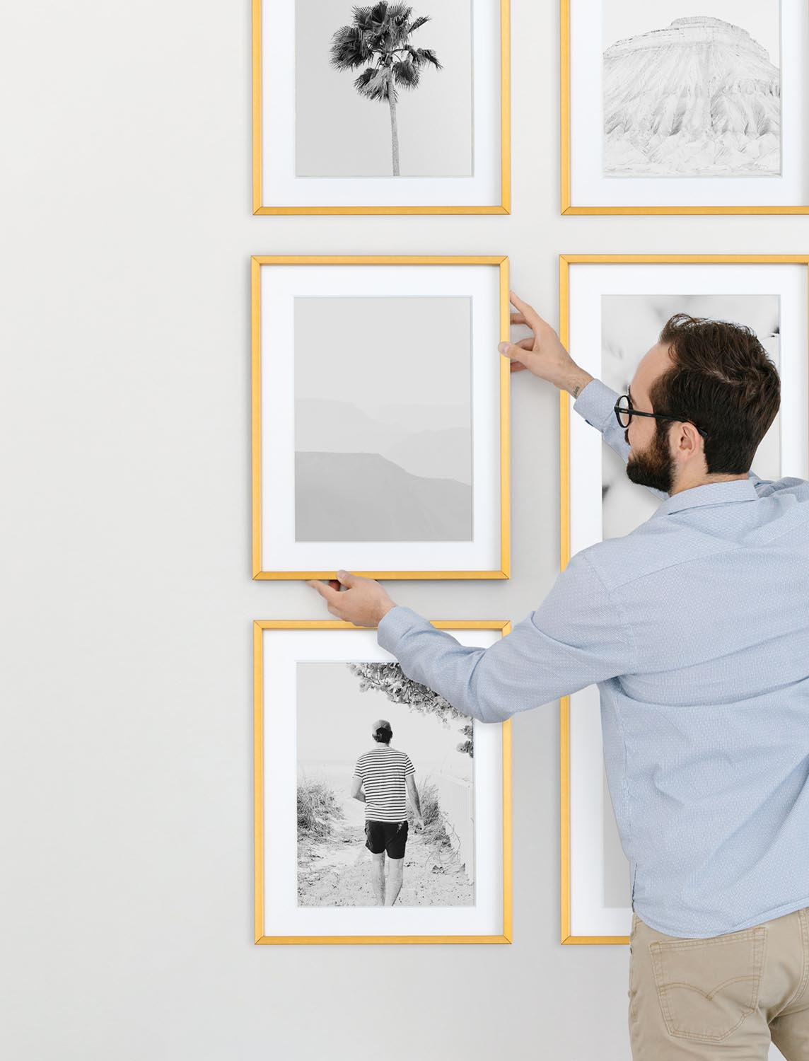Man hanging framed black and white photo to complete gallery wall