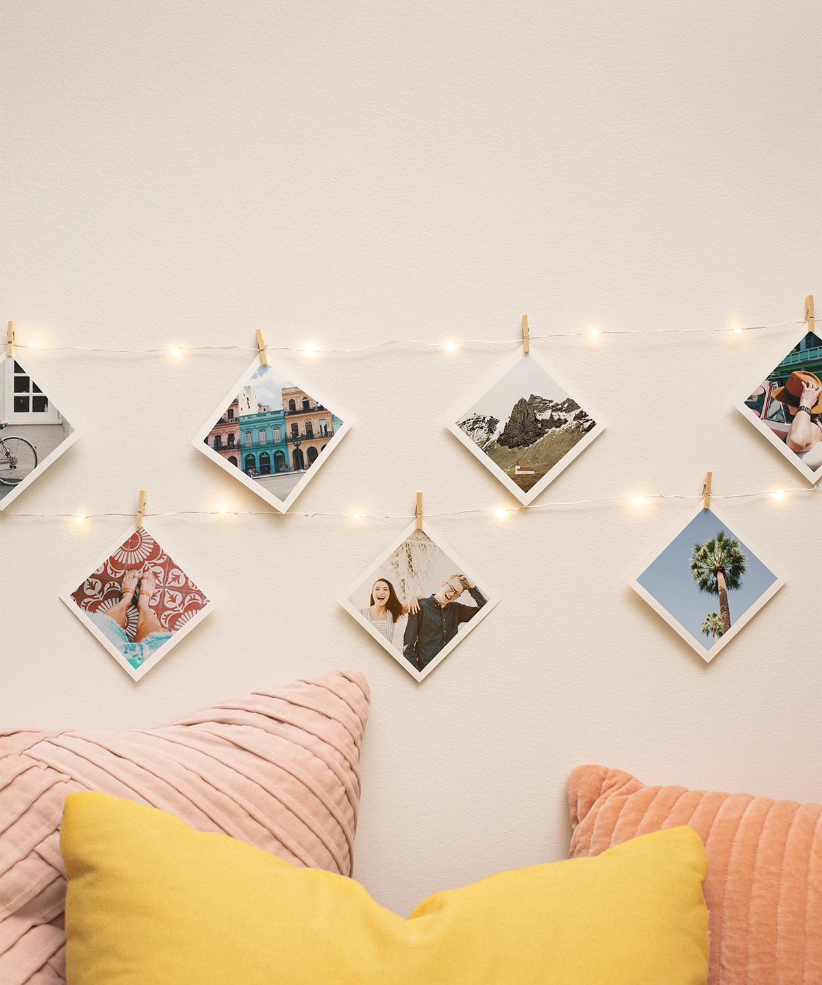 Photo prints hanging from string lights on wall