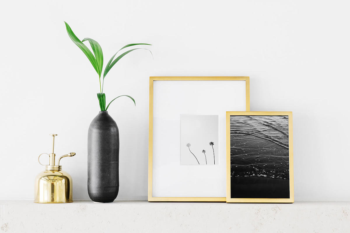 Mantle adorned with small tabletop frames and other decor
