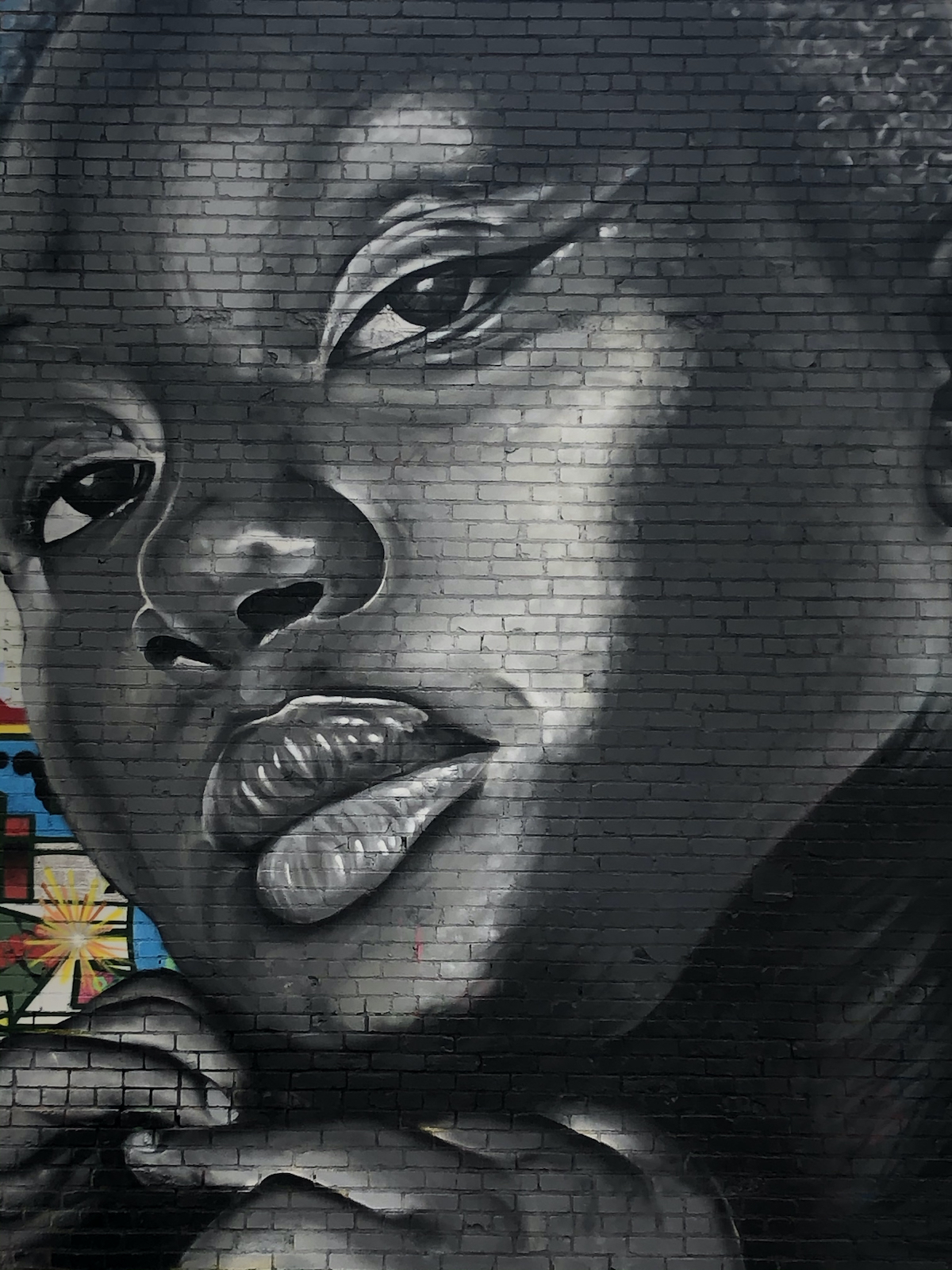 A mural of a black woman displayed on the side of a building