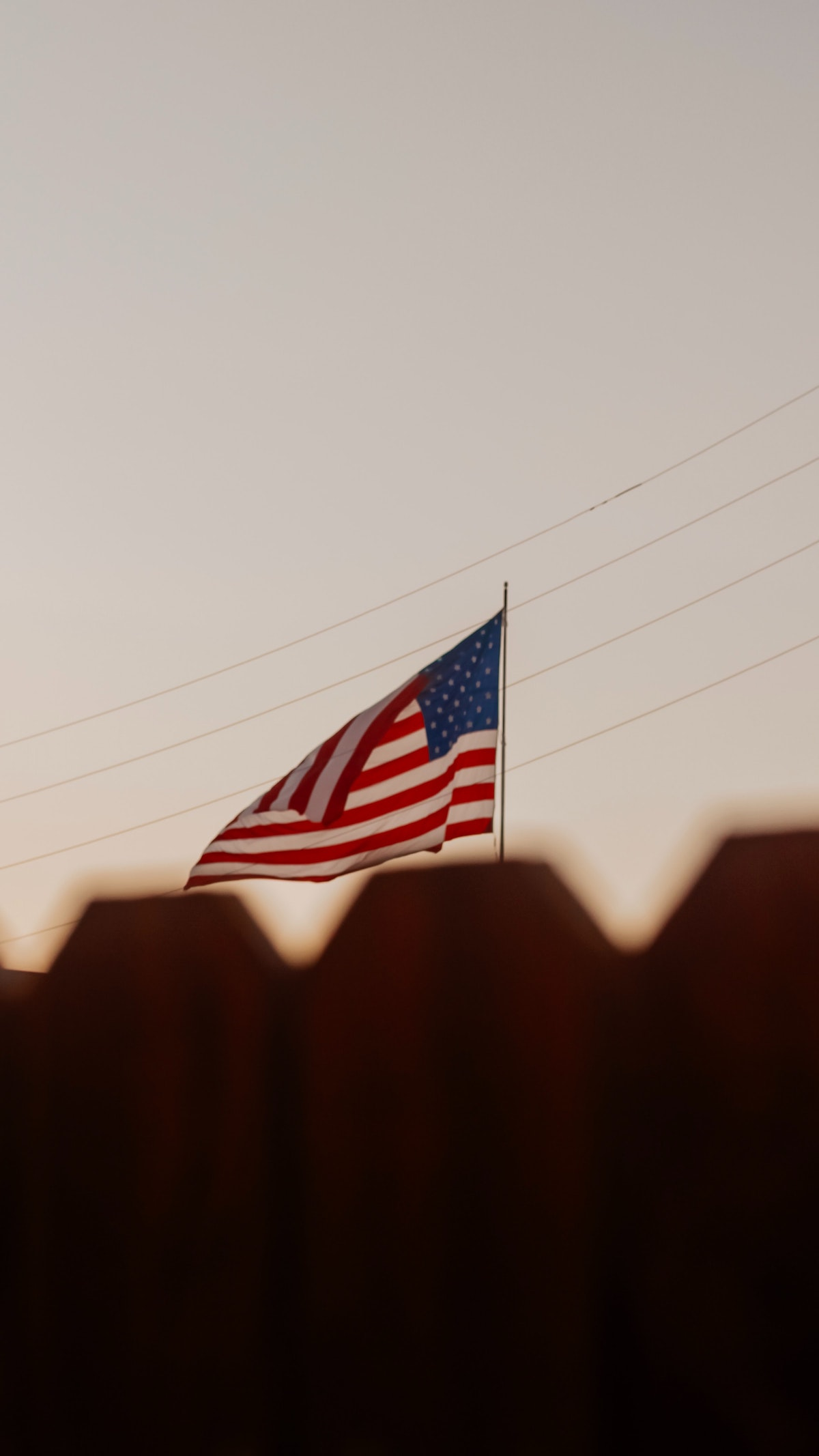 A photo of the American flag displayed just above the top of a fence in the foreground