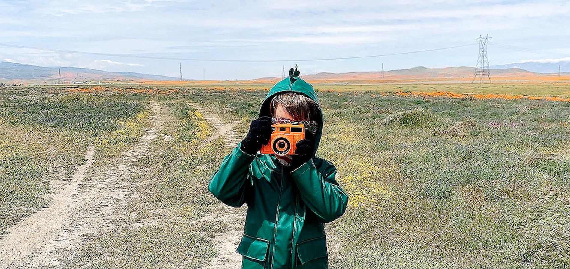Child pointing camera at camera while standing in open pasture