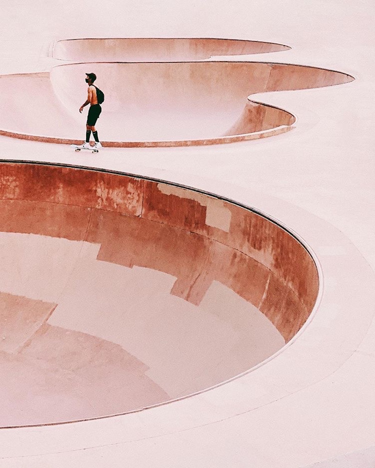 A skateboarder riding between two skate bowls with a red filter on the shot