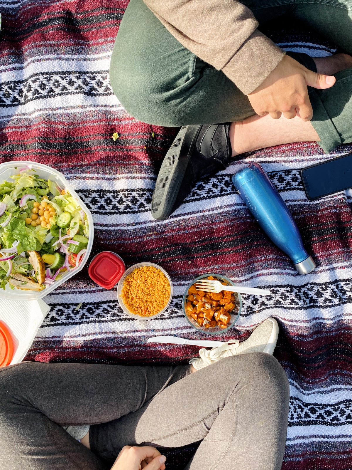 A meal laid out on a picnic blanket