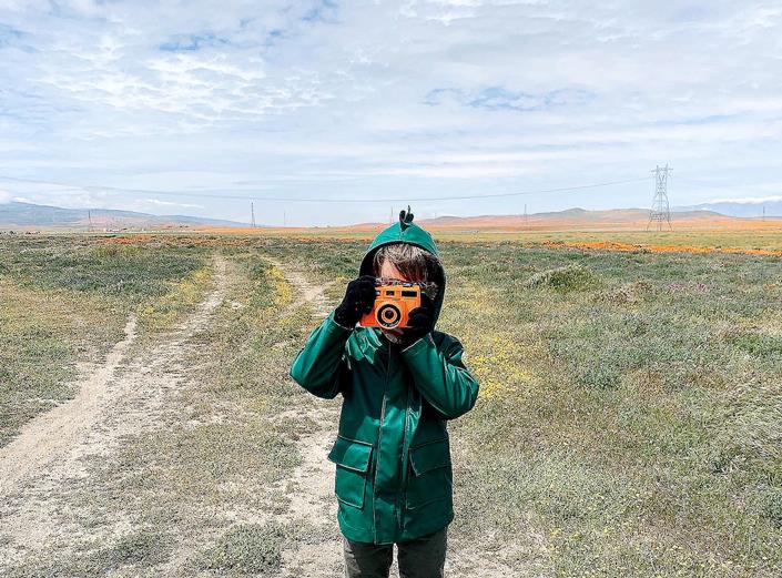 Little boy holding toy camera in wildflower field