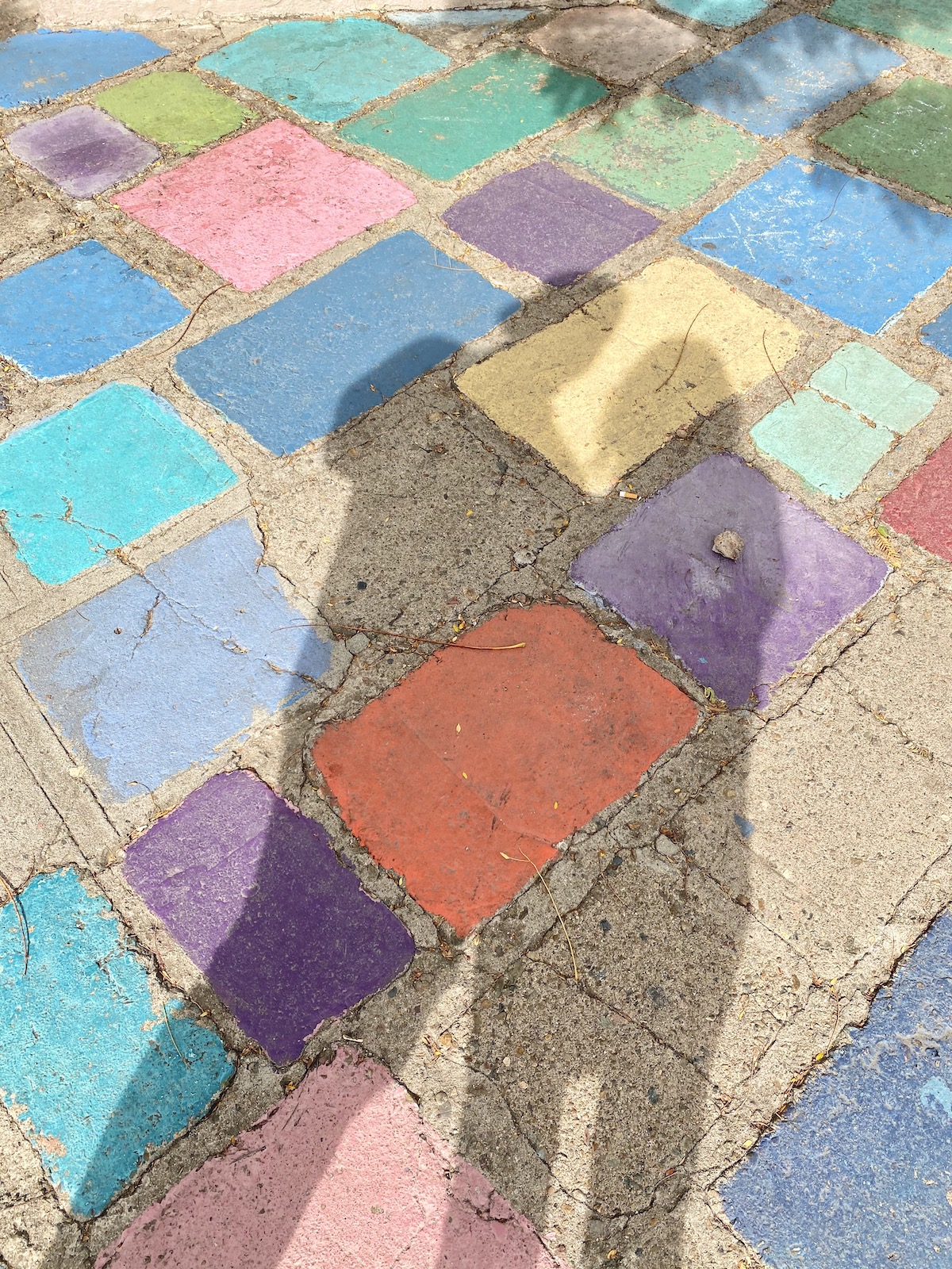 Shadows of the photographer displayed on a multi-colored cement tile floor