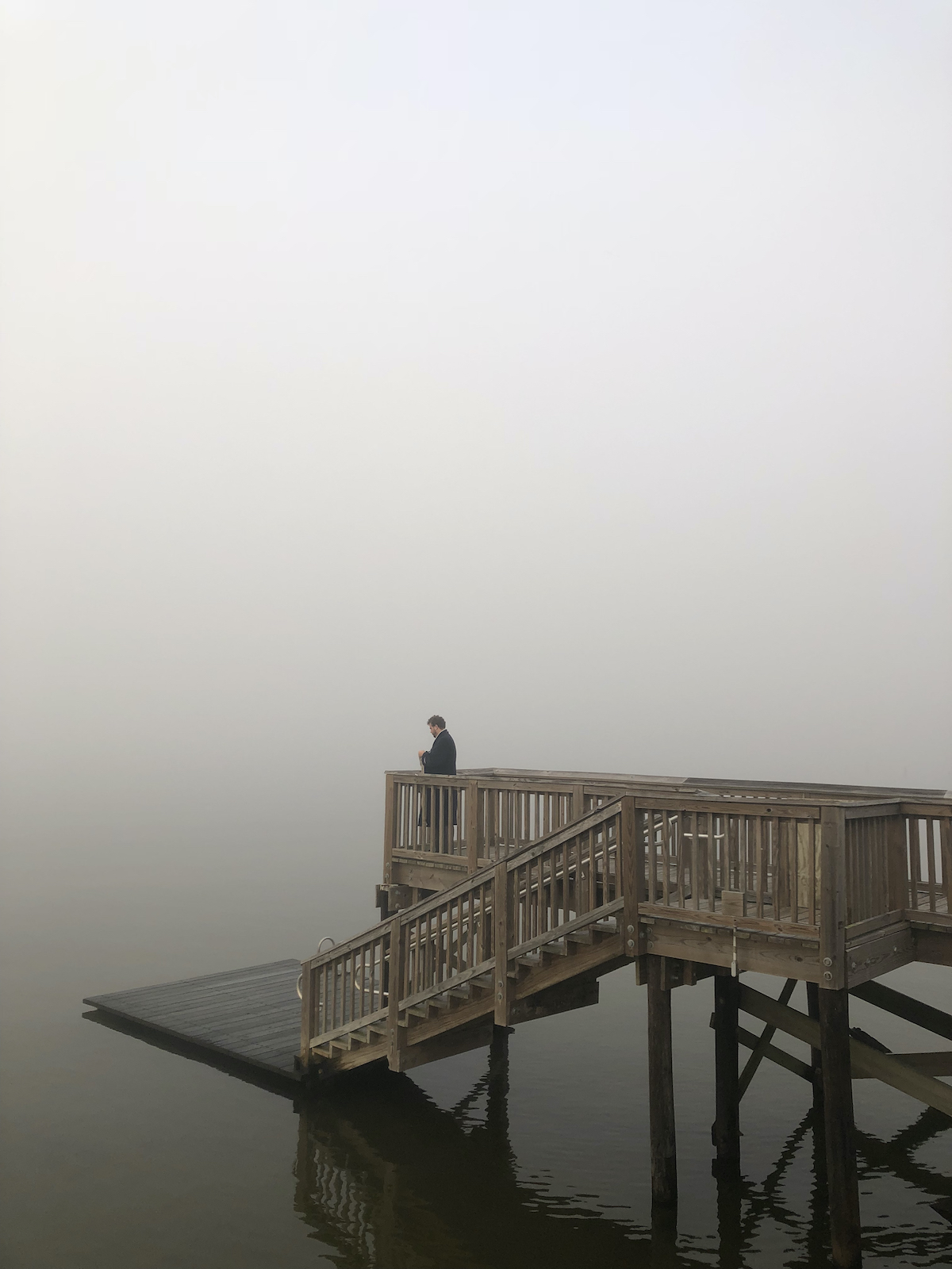 A dock in the water with a wooden walkway with a man staring over the edge in to the beyond