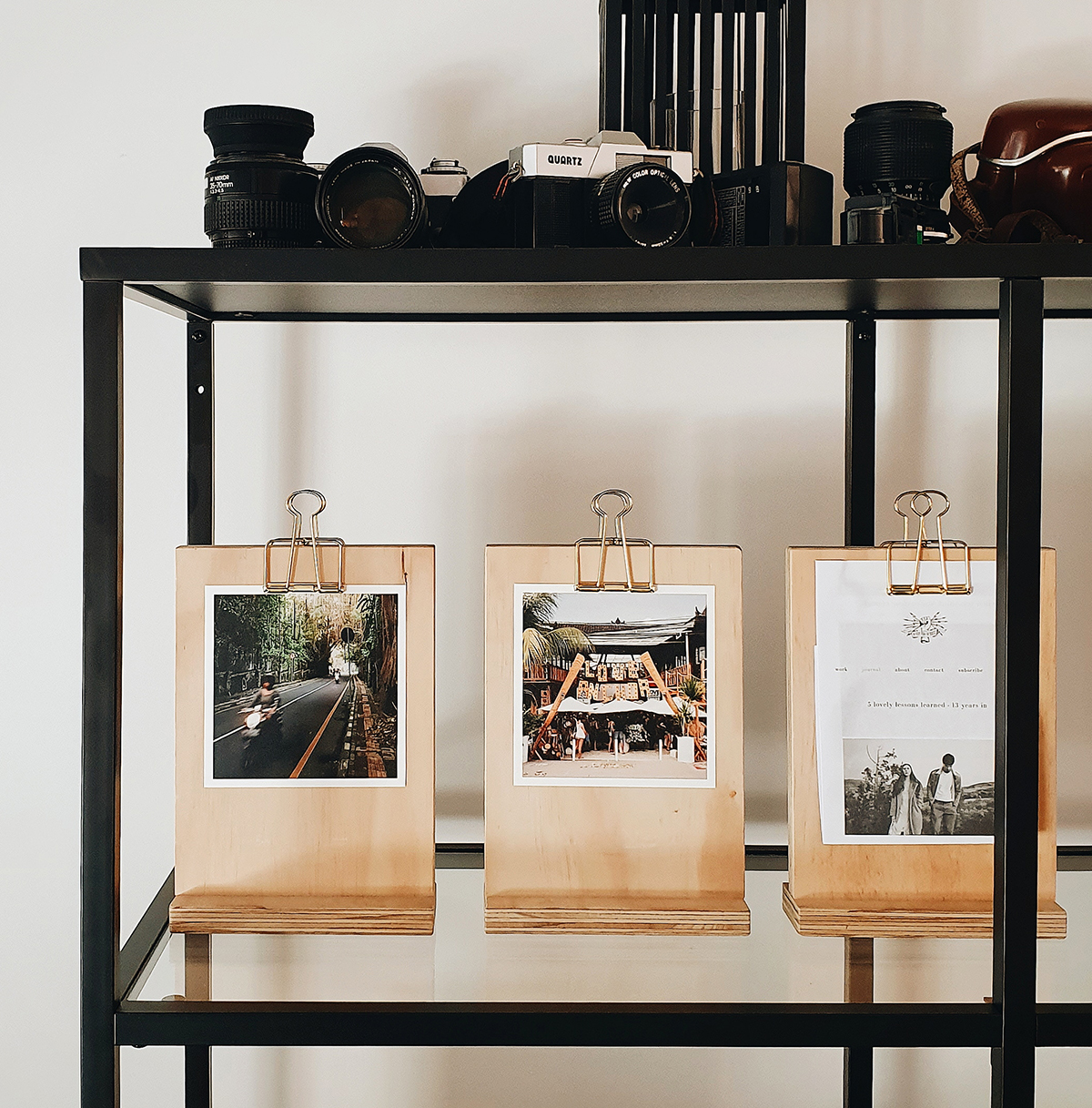 Unique wooden photo holders lined on a shelf and holding square prints