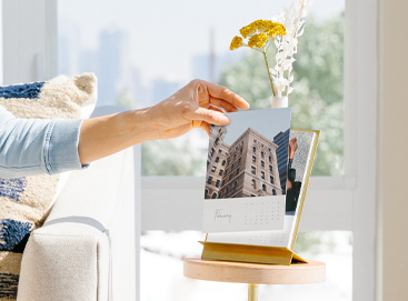 Woman changing the month on a desktop calendar she created with her own cityscape photos