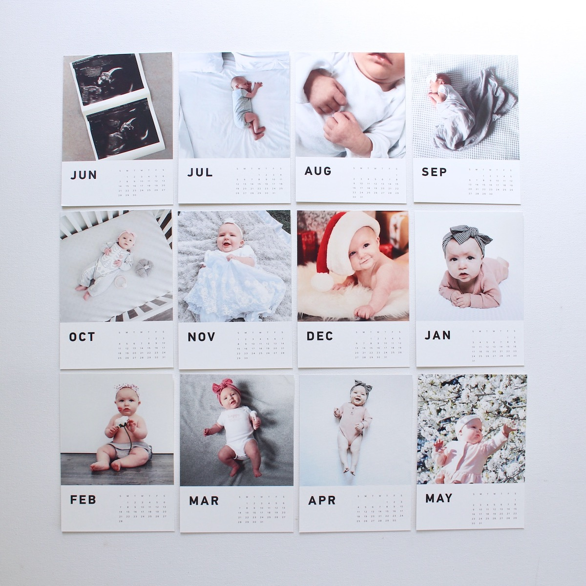 Calendar pages featuring baby photos laid out in grid