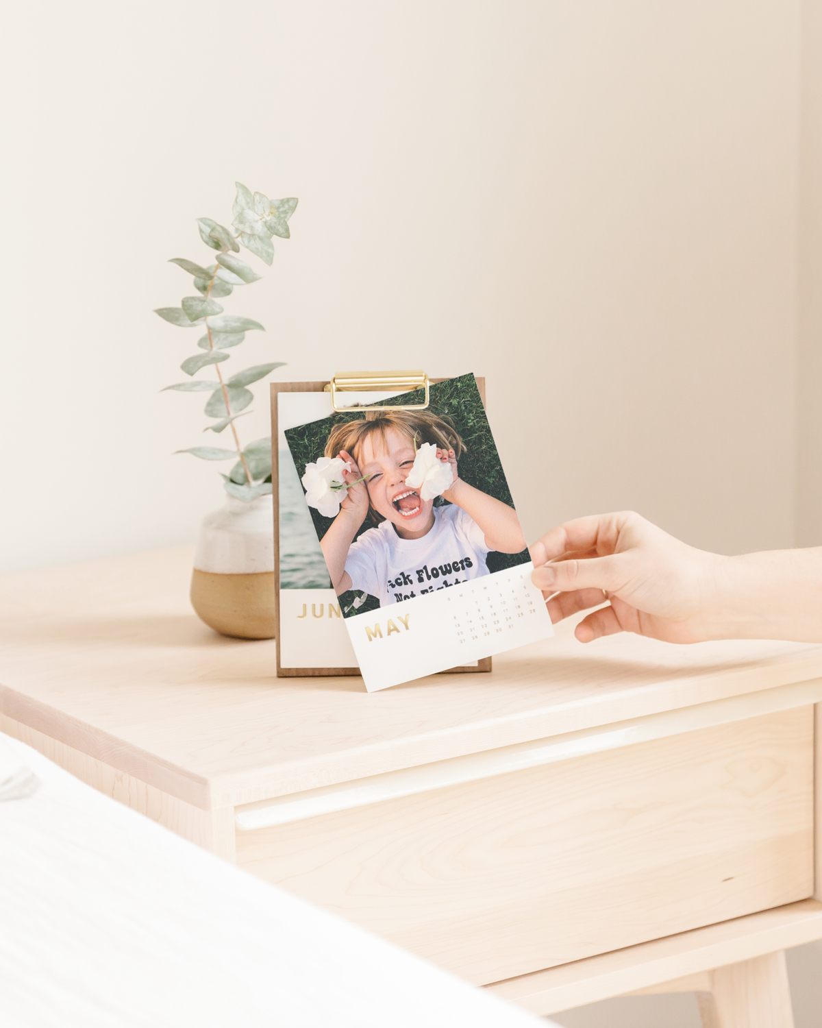 Desktop calendar on nightstand featuring playful photo of young child holding flowers