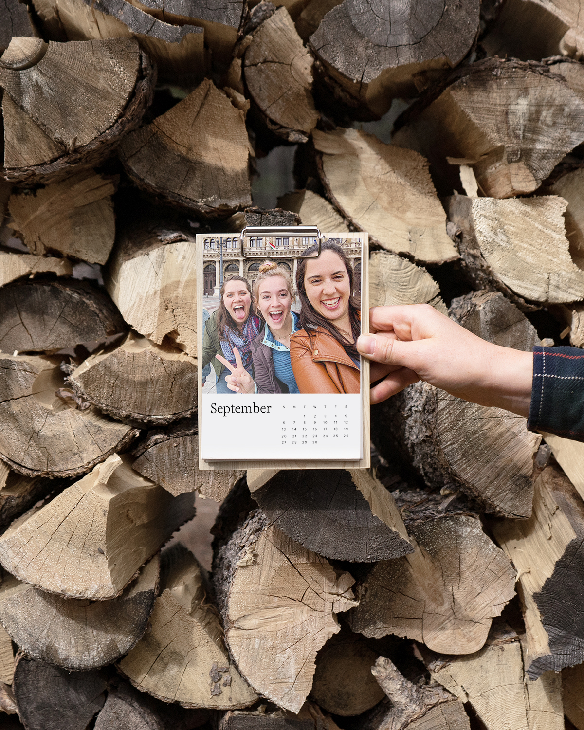 Hand holding up photo calendar with selfie of three friends featured