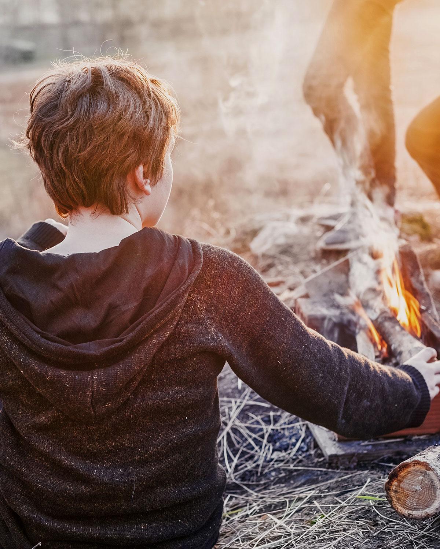 Boy tending a campfire