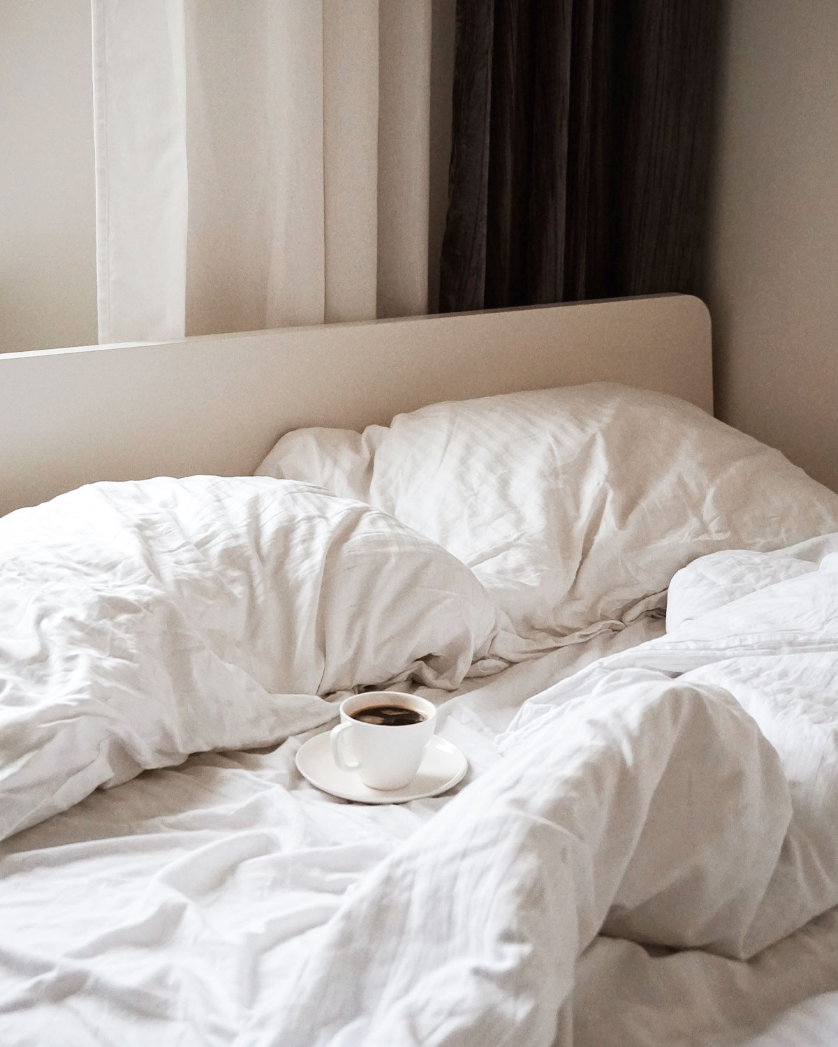 Cup of coffee in an empty unmade bed