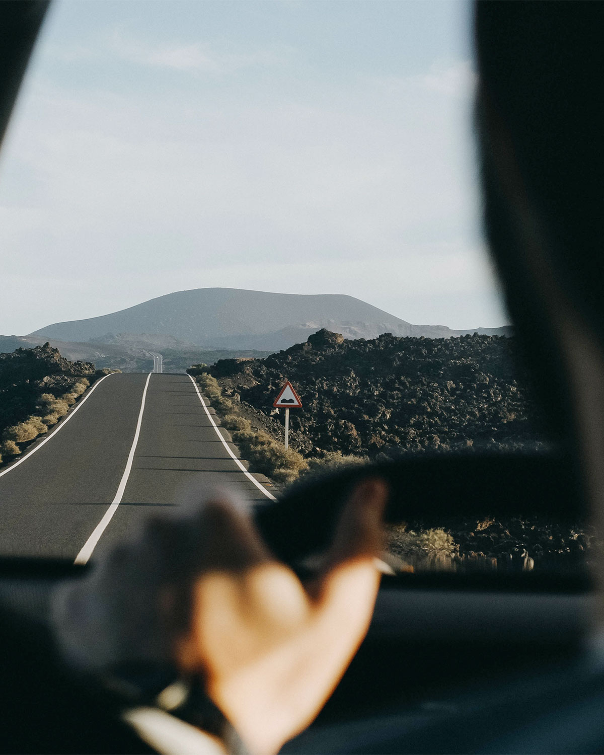 Driver's view of lush landscape along a remote road on a road trip