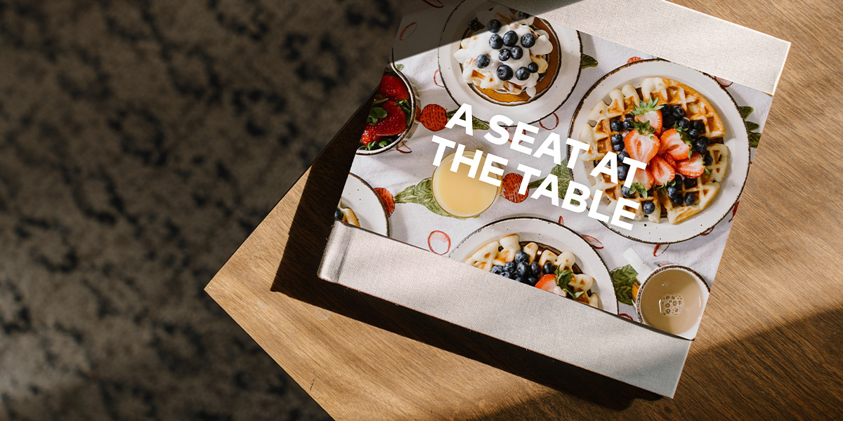 Collaborative cookbook titled A Seat at the Table with photos of waffles on cover