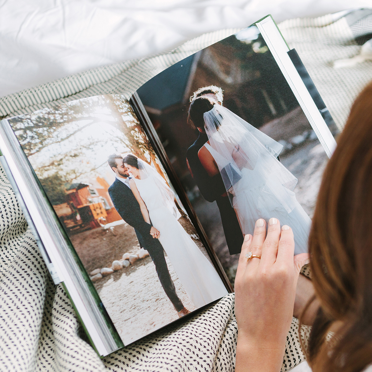 Woman flipping through interior pages of hardcover wedding photo book
