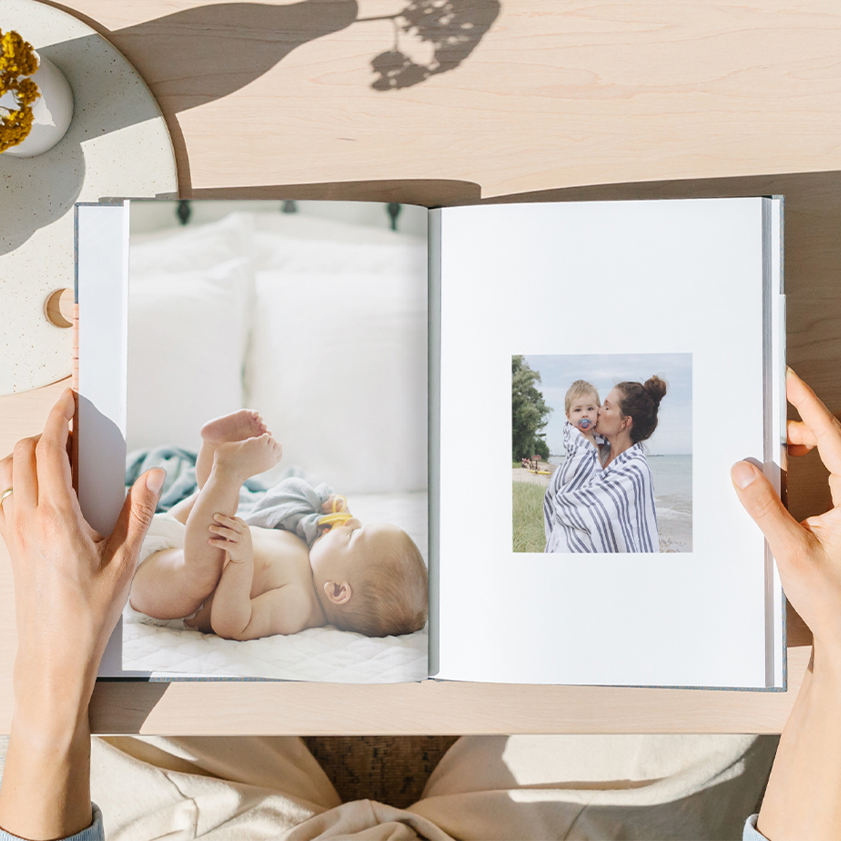 Interior of hardcover photo books showing two different layouts featuring baby photos
