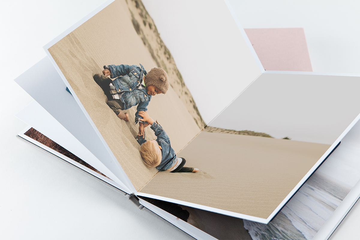 Layflat Photo Album opened to center panoramic spread of two little boys playing in sand