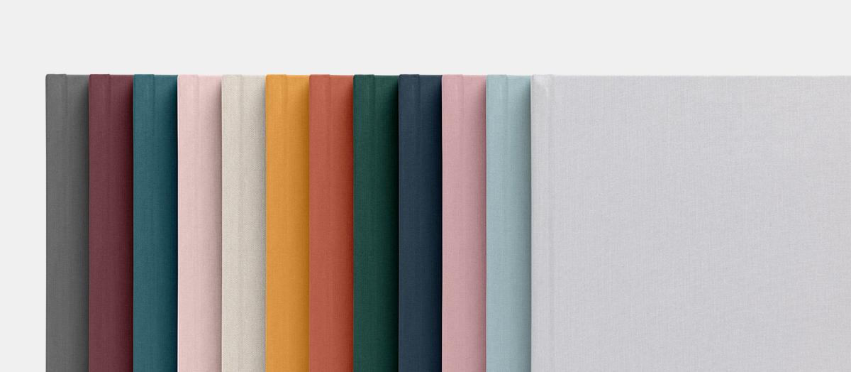 12 different colors of layflat albums laid out in color spectrum