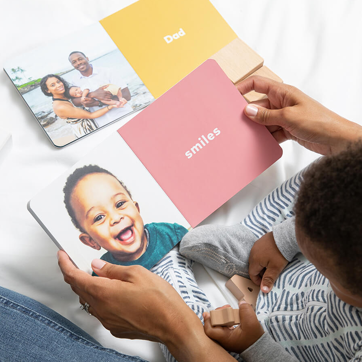 Mother and child reading baby board book opened to a page with the word smiles
