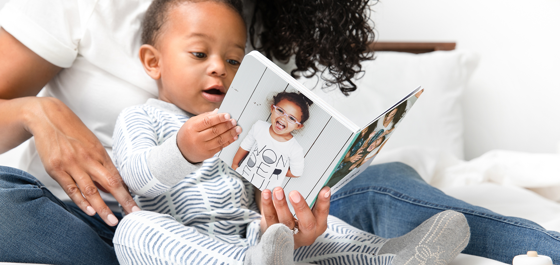 Baby holding board book and reading with mother