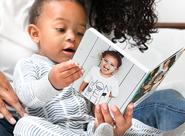 Little boy reading Artifact Uprising Baby Board Book with mother