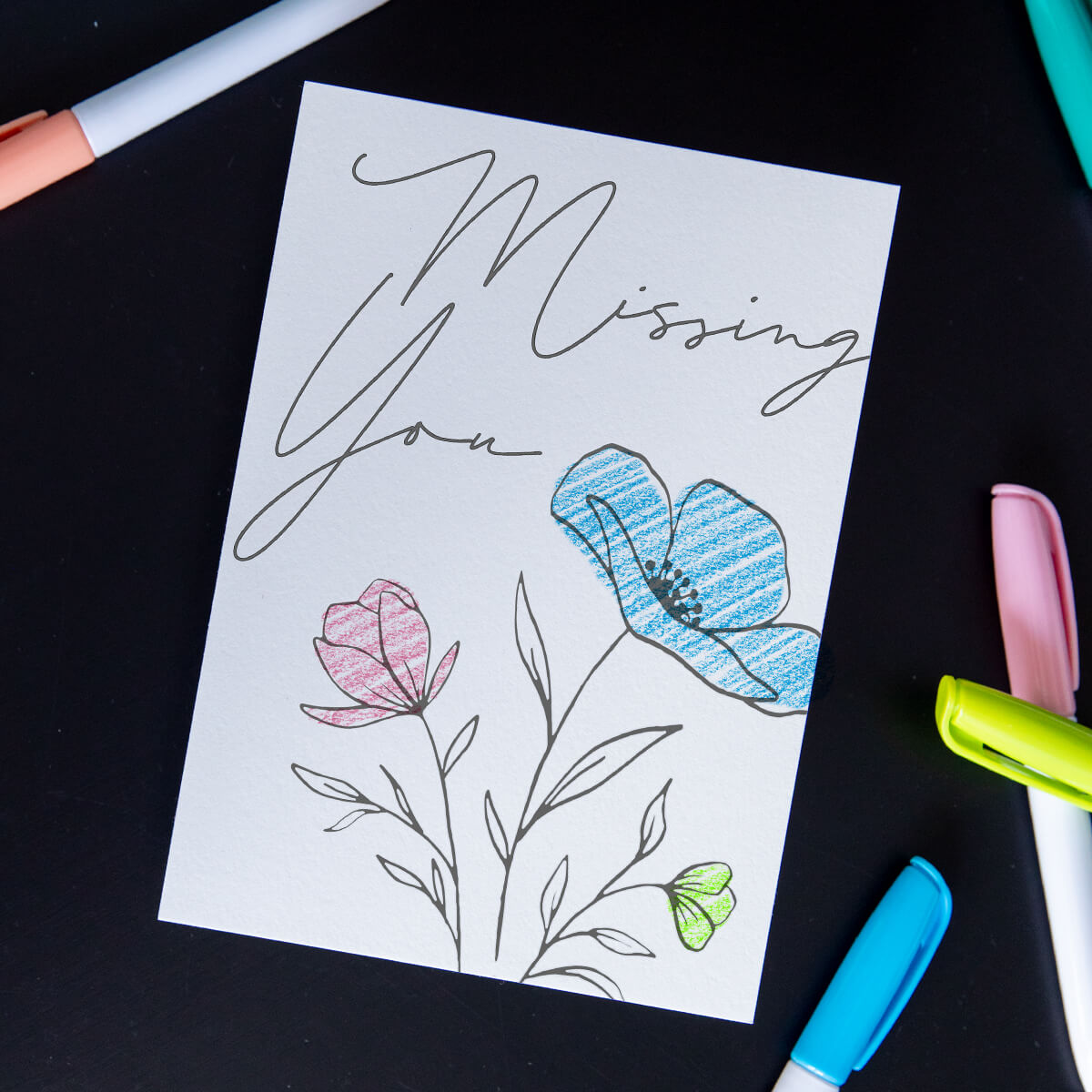 DIY postcard of black and white sketch of flowers that has been colored in by recipient