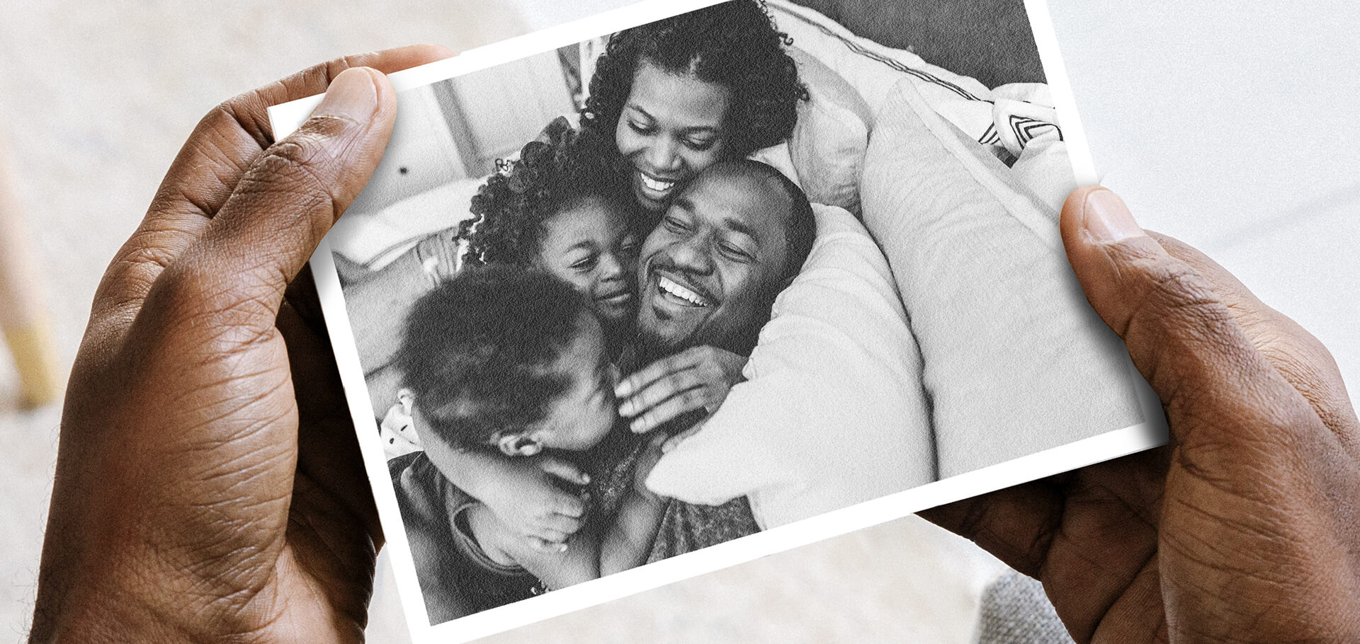 Hands holding DIY postcard with photo of family laughing and lounging on bed