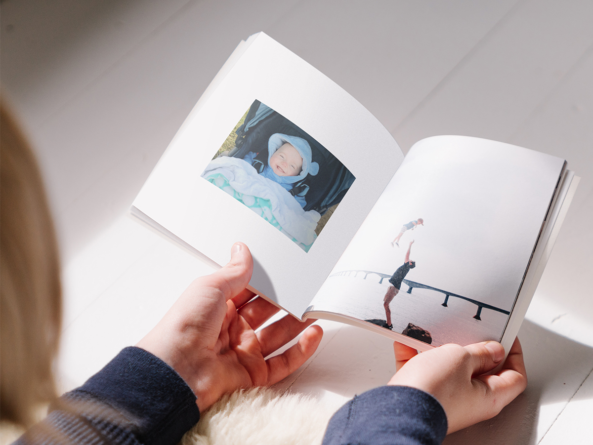 Softcover Photo Book opened to photo of baby on left page and father and toddler on right page