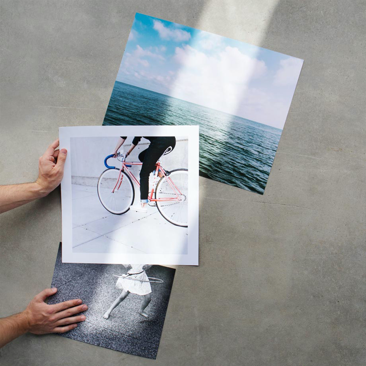 Three giclée prints on surface with ray of light illuminating them