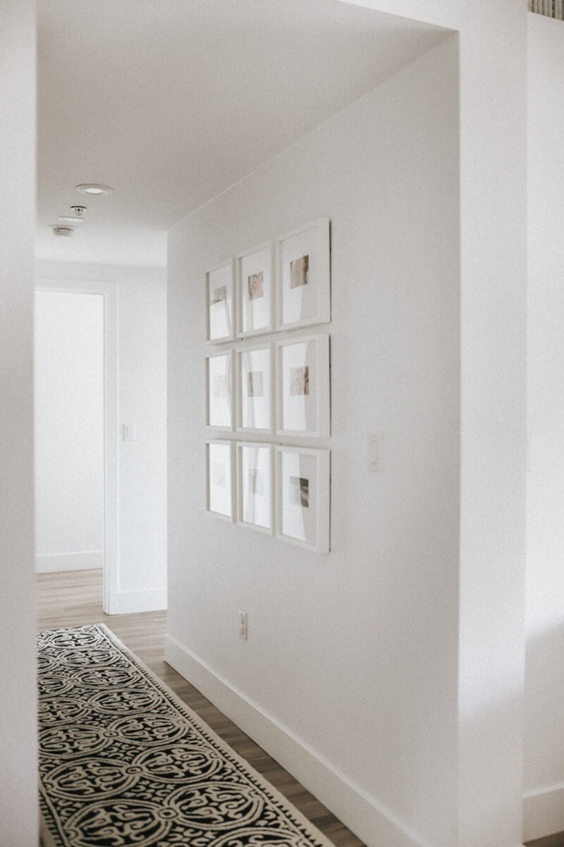 Gallery wall of family photos in brightly lit hallway