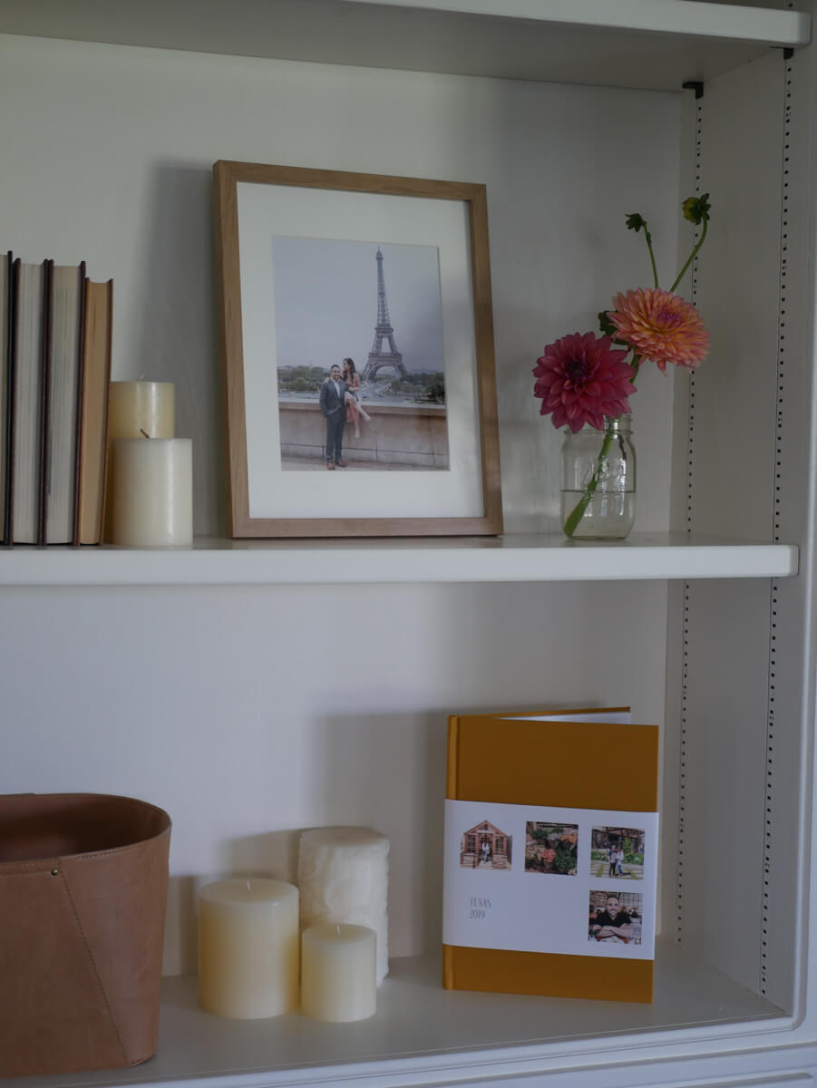 Recessed wall shelves with travel album, framed photo, candles, and other decor