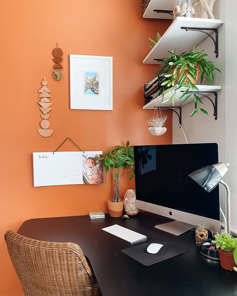 Home office featuring plants, orange wall, and Artifact Uprising Modern Wall Calendar