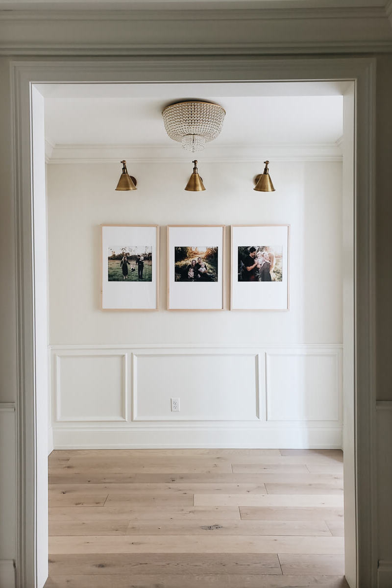 Three large framed family photos hung side by side in empty room