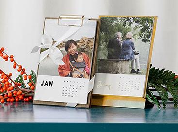 Artifact Uprising Walnut Desktop Calendar next to Brass Easel & Calendar