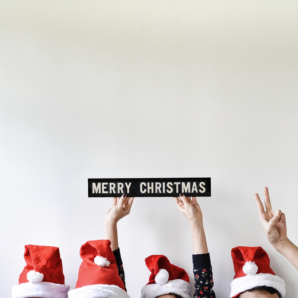 Tops of four heads with Santa hats and hands holding up Merry Christmas sign