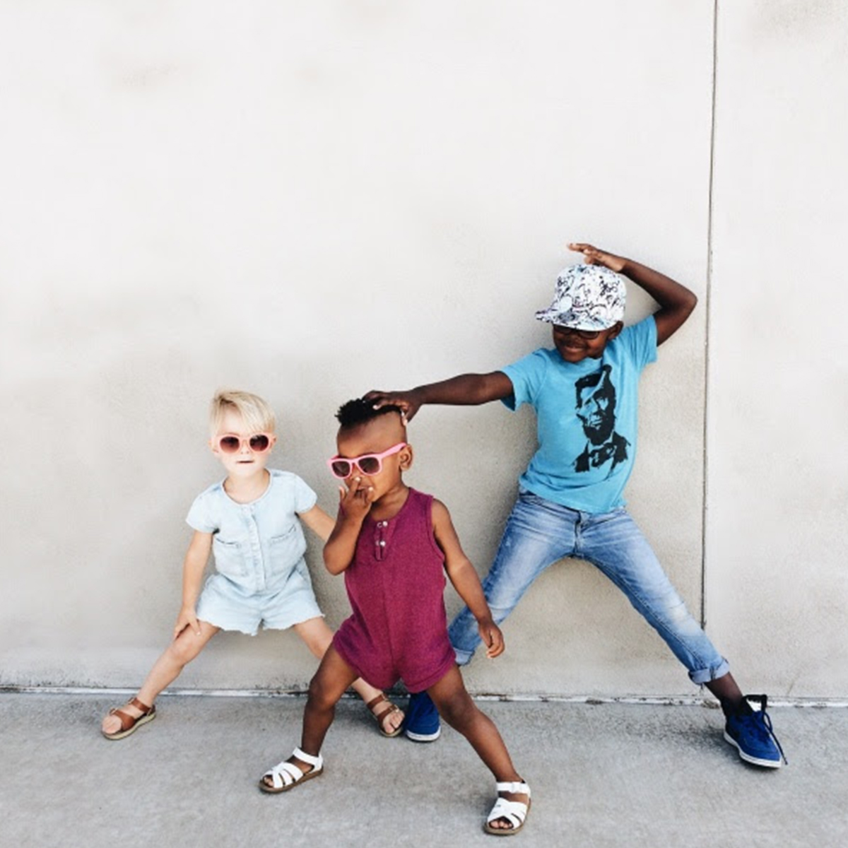 Trio of children in sunglasses striking dance poses