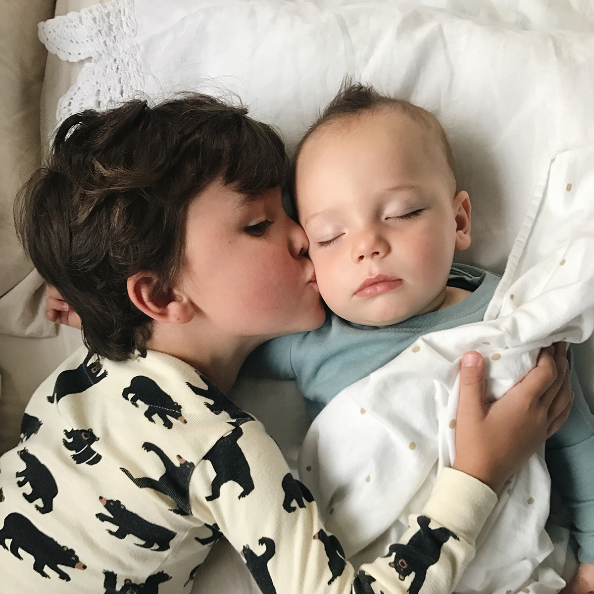 Little boy kissing his sleeping baby brother on the cheek