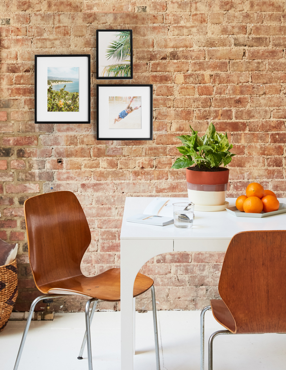 Golden Pothos on dining table with Metal Tabletop Frames hanging on the brick wall behind