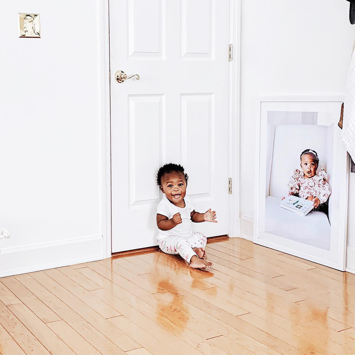 Baby sitting in front of enlarge photo of self resting on ground