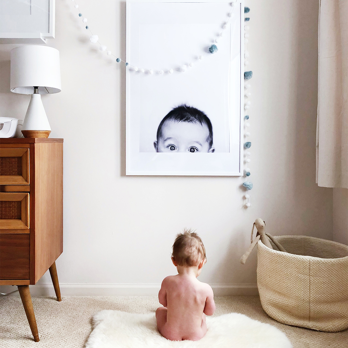 Baby sitting in front of enlarged photo of self on the wall