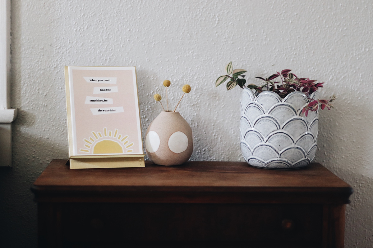 Brass Easel Print Display with inspiring words on dresser next to plants