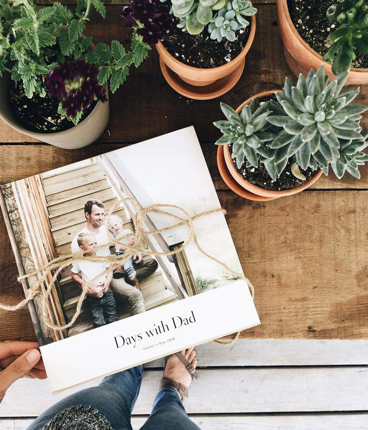Hardcover Photo Book titled days with dad on table next to succulents