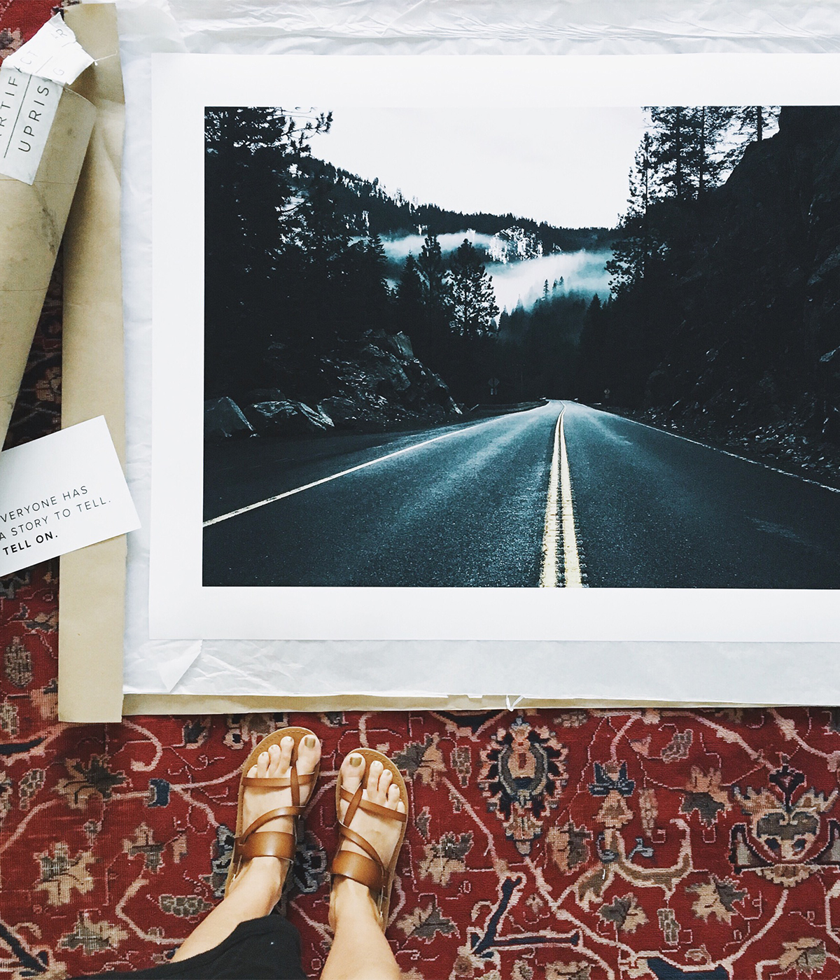 Large Format Print still in packaging unrolled at woman's feet