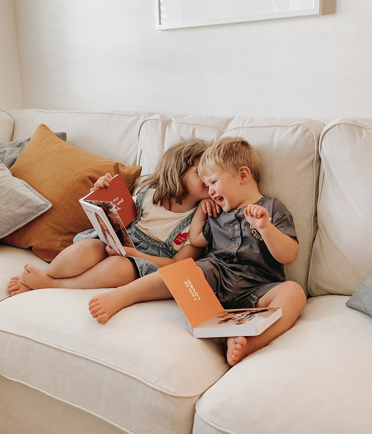 Young siblings laughing as they read board books